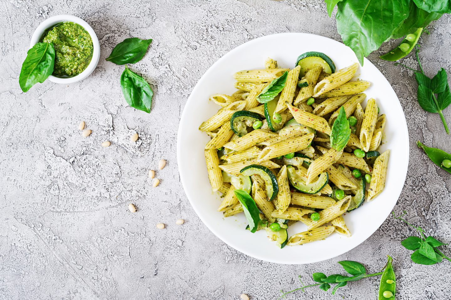 penne-pasta-with-pesto-sauce-zucchini-green-peas-and-basil-italian-food-top-view-flat-lay
